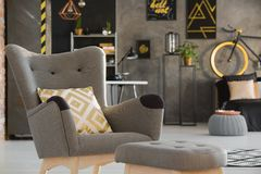 Patterned yellow pillow on grey armchair near stool in teenager` royalty free stock photo