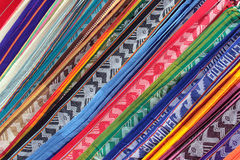 Patterns and Angles. In this abstract pattern formed by a pile of table linens made of alpaca wool stacked for sale at the outdoor craft market in Otavalo stock images
