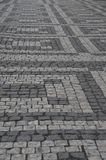 Patterns in a cobblestone street. A cobblestone street with geometrical patterns made from light and dark grey cobbles Royalty Free Stock Image