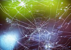 The patterns of cracks on glass. Cracks on glass on a colored background Stock Images