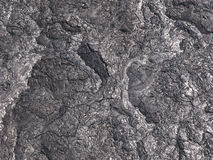 Patterns cracks and shapes emerge from this close up portion of black solidified lava. On the island of Hawaii royalty free stock images
