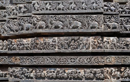 Patterns of the Hindu temple walls with vedic and puranic scenes. 12th centur Hoysaleshwara temple in Halebidu, India. Royalty Free Stock Photo