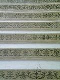 Patterns on marble stairs. A set of old marble stairs. A variety of green-blue patterns are on the front. The marble is white, and cracked with age stock photos
