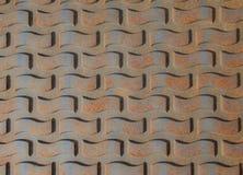 Patterns on rusty iron manhole cover. Background stock photo