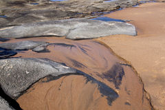 Patterns in Sand and Rocks at Low Tide on Shoreline Stock Images