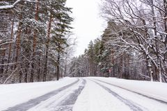 Patterns on the winter highway in the form of four straight lines. Snowy road on the background of snow-covered forest. stock image