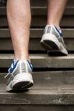 Pattes d'homme courant sur des escaliers Image stock