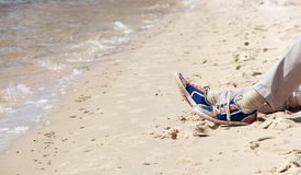 Pattes d'homme sur la côte de sable Image libre de droits