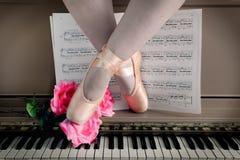 Pattes de ballet dans Pointe sur le piano photo libre de droits