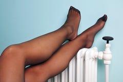 Pattes de bas de Womans sur un radiateur Image stock