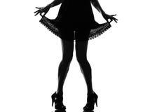 Pattes de femme de silhouette tirant sa robe d'été Image libre de droits
