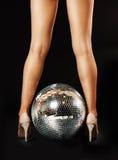Pattes de femme et bille de disco Photo stock