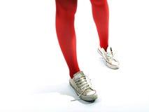 Pattes de jeunes filles dans les collants rouges et de vieilles espadrilles Image stock