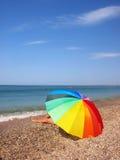 Pattes de parapluie et de femme de plage d'arc-en-ciel images stock