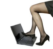 Pattes de womans d'affaires sur l'ordinateur portatif photos stock