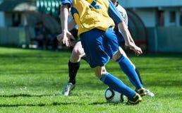 Pattes du football sur le duel du football photographie stock