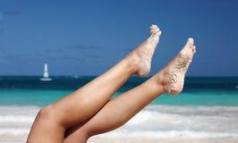 pattes du `s de femme sur le fond tropical de plage photos stock
