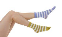 Pattes femelles dans les chaussettes de différentes couleurs Photographie stock