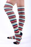 Pattes femelles dans stripy au-dessus des chaussettes de genou Images stock