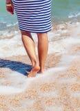 Pattes femelles sur la plage Jambes d'une fille dans une robe rayée en mer Jambes femelles avec une pédicurie rouge en mer Image stock