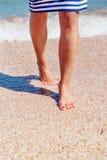 Pattes femelles sur la plage Jambes d'une fille dans une robe rayée en mer Jambes femelles avec une pédicurie rouge en mer Photographie stock libre de droits