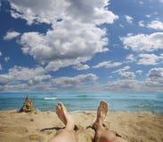 Pattes mâles au-dessus de plage tropicale Photographie stock libre de droits