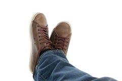 Pattes mâles dans le mensonge d'espadrilles et de jeans Photos stock