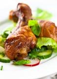 Pattes rôties de poulet sur des légumes Image libre de droits