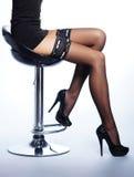 Pattes sexy d'un jeune femme dans les bas noirs Photo stock