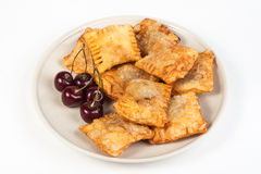 Patties stuffed with fresh cherries. On a plate royalty free stock photos