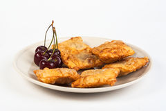Patties stuffed with fresh cherries. On a plate Royalty Free Stock Photography
