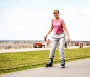 Pattinaggio a rotelle attivo della giovane donna all'aperto immagine stock