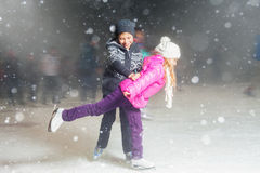 Pattinaggio su ghiaccio felice alla pista di pattinaggio sul ghiaccio, notte dei bambini di inverno Immagine Stock Libera da Diritti