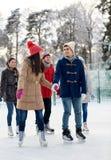 Pattinaggio su ghiaccio felice degli amici sulla pista di pattinaggio all'aperto Immagini Stock