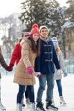Pattinaggio su ghiaccio felice degli amici sulla pista di pattinaggio all'aperto Immagine Stock