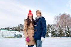 Pattinaggio su ghiaccio felice delle coppie sulla pista di pattinaggio all'aperto Immagine Stock Libera da Diritti