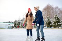 Pattinaggio su ghiaccio felice delle coppie sulla pista di pattinaggio all'aperto Immagini Stock