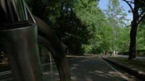 Pattinamenti e giri della bicicletta della montagna lungo il percorso a terra stock footage