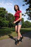 Pattinare di rullo con le gambe lunghe sexy della donna di divertimento di estate fotografie stock