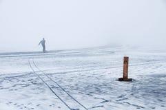 Pattinare di velocità sul ghiaccio di fusione in nebbia di inverno Fotografia Stock