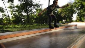 Pattinare in-linea aggressivo nello skatepark all'aperto Giovane giro dell'atleta sulle lame del rullo Frantumazioni del ragazzo  stock footage
