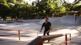 Pattinatore in-linea del rullo che fa i trucchi nello skatepark concreto all'aperto con il bello fondo verde del parco, movimento archivi video