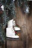 Pattini da ghiaccio con i rami sempreverdi Immagini Stock