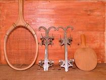 Pattini da ghiaccio d'annata, racchetta di tennis e racchetta di ping-pong su fondo di legno Retro raket di tennis dei pattini da Immagine Stock