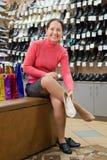 Pattini di prova della donna al negozio di pattini fotografie stock libere da diritti