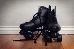 Pattini di rullo degli uomini sul pavimento di legno duro fotografia stock libera da diritti