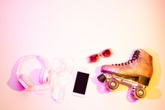 Pattini di rullo, smartphone, cuffie ed occhiali da sole fotografia stock