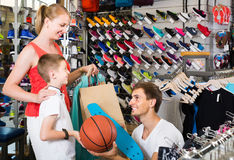 Pattino d'acquisto della donna e dell'uomo per il figlio nel negozio di sport Fotografie Stock Libere da Diritti