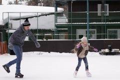 Pattino della figlia e di papà sulla pista di pattinaggio sotto il cielo aperto un giorno di inverno fotografia stock libera da diritti