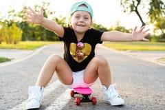 Pattino di guida del bambino nel parco di estate Bambina che impara guidare il bordo del pattino Sport all'aperto attivo per la s fotografie stock